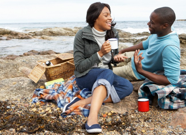 happy black-couple-having-picnic-on-rocks-near-beach-smaller